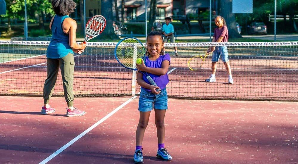 child holding tennis racket